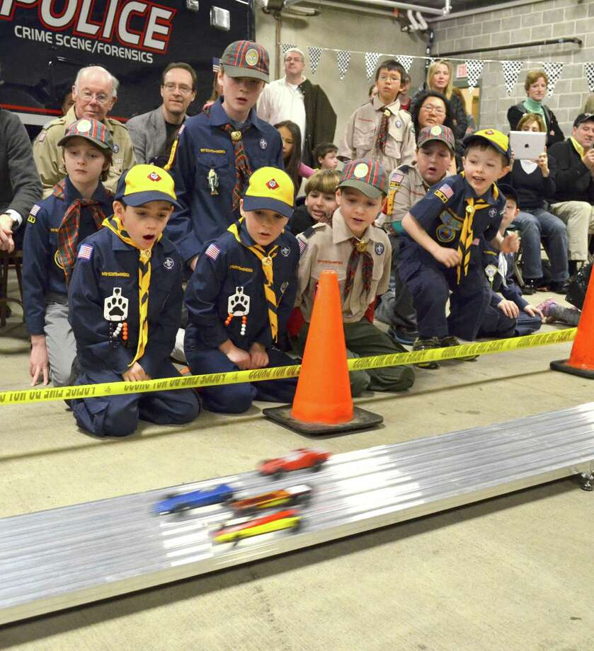 Local Cub Scouts recently took part in the Greenwich Pinewood Derby Championship, an annual model car race where Scouts make their own cars and vie for the title of fastest racer. Above, Cub Scouts (from left) John Sarubbi, Carl Griffasi, David Levine and Ethan Miklautsch cheer for their favorite cars as they speed down the track, which was set-up at the Greenwich Police Station. Photo: Jessica Reid/Contributed Photos