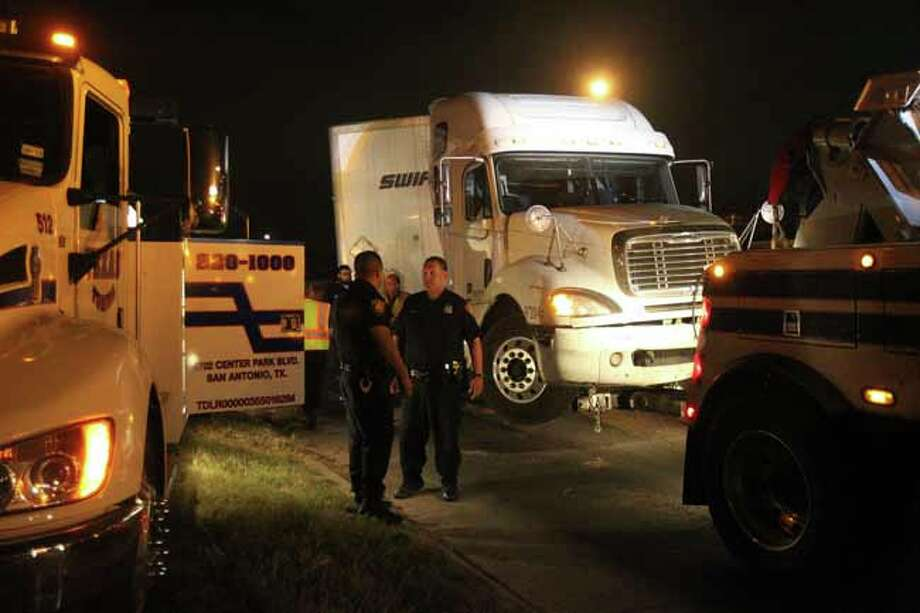 San Antonio police work early Wednesday March 20, 2013 at the interchange of IH-35 northbound and IH-10 eastbound near Burbank High School where an 18-wheeler tractor trailer rig veered off the connecting ramp onto the median and feeder road at about 2:30 a.m. . Police at the scene were not sure why the driver veered off the highway and police briefly closed down the connecting ramp connecting the two interstate highways to remove the truck. The driver was not injured and the scene was cleared by 7:15 a.m. . Photo: JOHN DAVENPORT, SAN ANTONIO EXPRESS-NEWS / ©San Antonio Express-News/Photo may be sold to the public