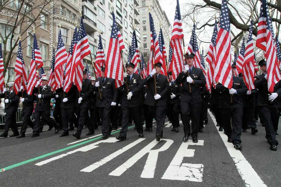 Holding flags in memory of the 343 firefighters who lost their lives in the Sept. 11 attacks, members of the New York City Fire Department make their way up New York's Fifth Avenue as they take part in the St. Patrick's Day Parade Saturday, March 16, 2013. Photo: Tina Fineberg, AP / FR73987 AP