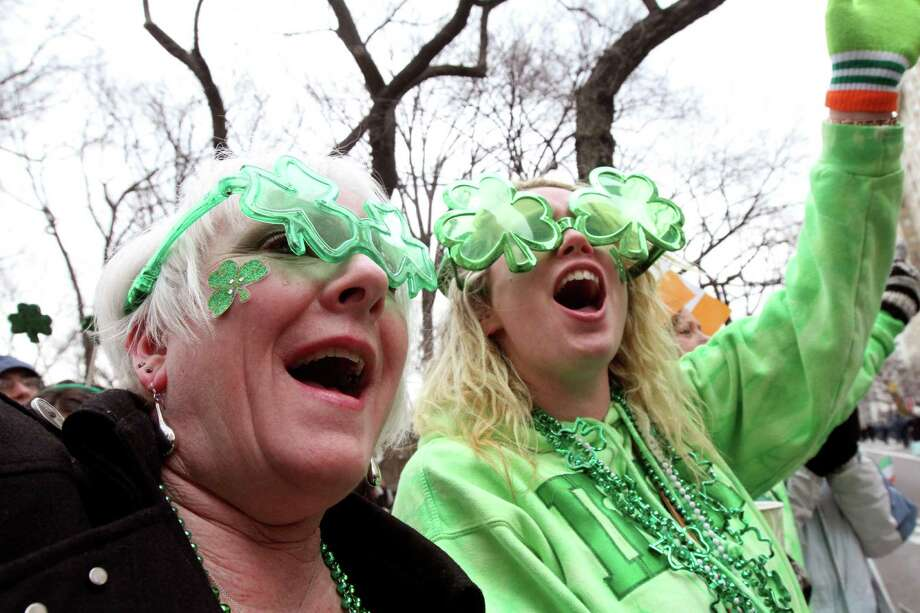 Kathy Brucia, of Bellmore, N.Y, left, and Kara Kerley, of Wantagh, N.Y., laugh as they watch the St. Patrick's Day Parade as it moves up New York's Fifth Avenue Saturday,  March 16, 2013. Photo: Tina Fineberg, AP / FR73987 AP