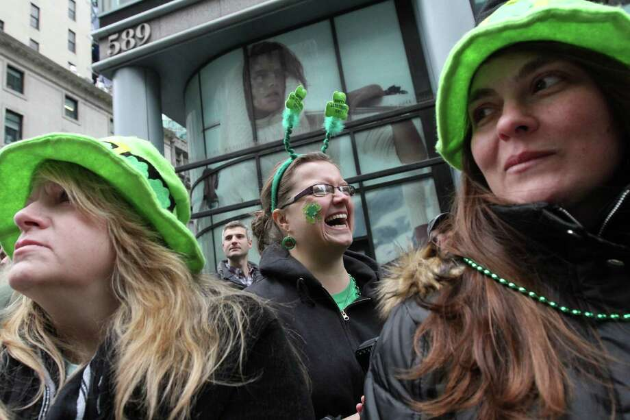 Donna Flanagan, of Palm Coast, Fla., left, her sister-in-law Cathleen Flanagan, of Setauket, N.Y., right, and others watch the St. Patrick's Day Parade as it makes it's way up New York's Fifth Avenue Saturday,  March 16, 2013. Photo: Tina Fineberg, AP / FR73987 AP