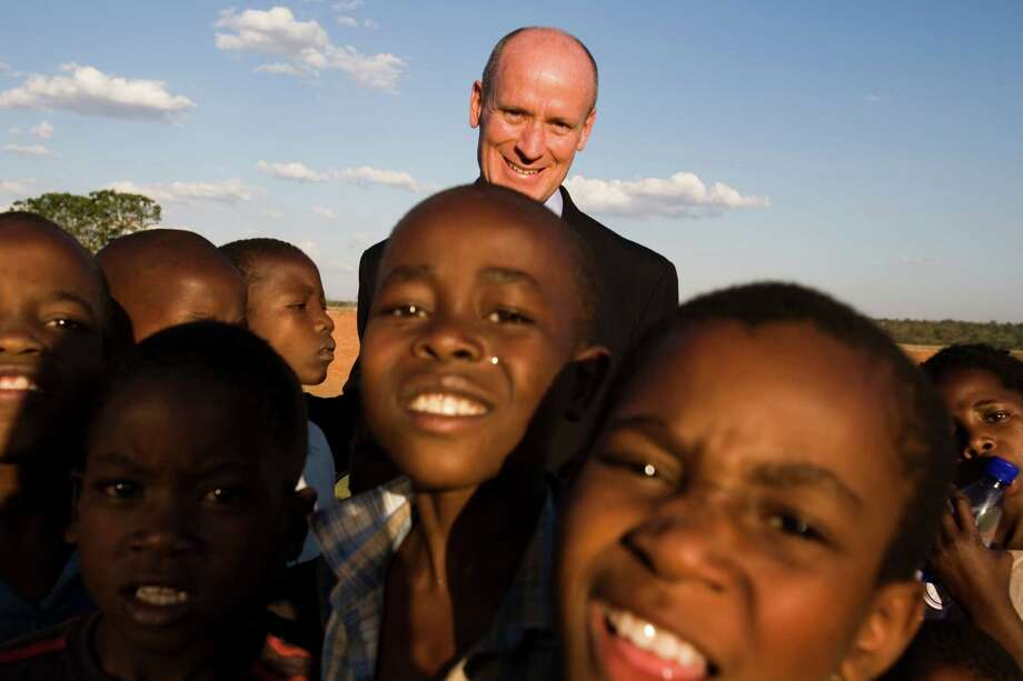 Dr. Mark Kline, president of the Baylor International Pediatric AIDS Initiative, is seen with a group of children during dedication ceremonies for the Baylor College of Medicine-Abbott Fund Children's Clinical Centre of Excellence in Lilongwe, Malawi in 2006. Photo: SMILEY N. POOL., Staff / Houston Chronicle