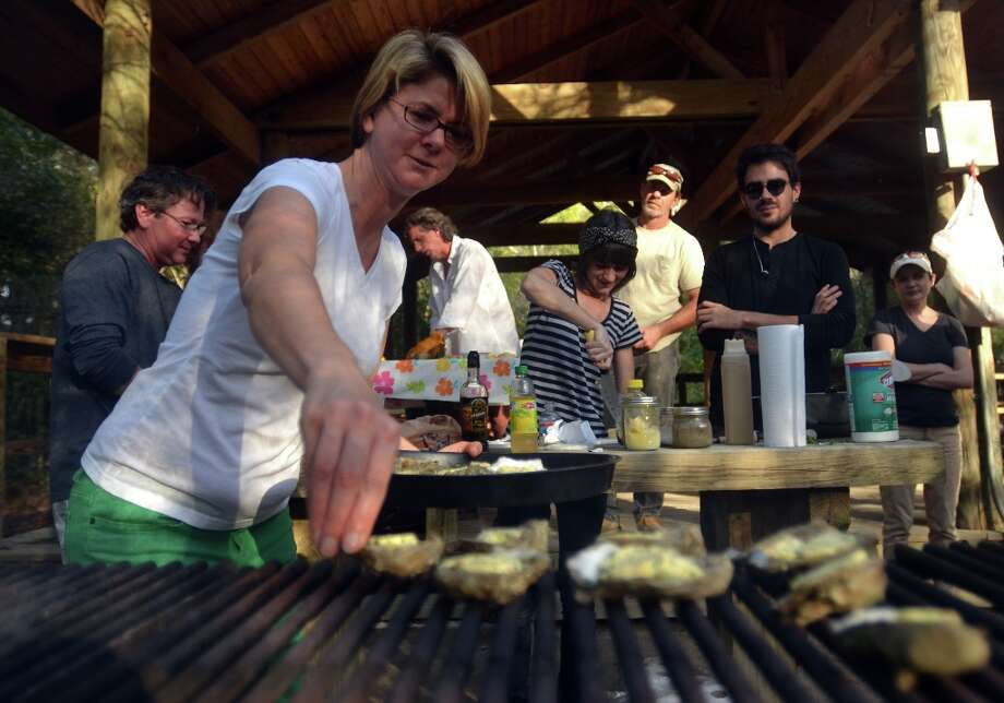 Rebecca Boone, founder of Slow Food Beaumont, places fresh Gulf oysters on the grill during Oysterfest. Beth Rankin/cat5 Photo: Beth Rankin / Beth Rankin