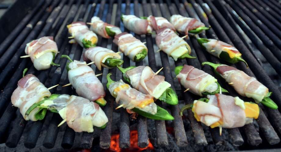 Local garden jalapenos stuffed with cheese and wrapped in bacon cook on the grill at Slow Food Beaumont's Oysterfest at Village Creek State Park in Lumberton on Jan. 25, 2013. Beth Rankin/cat5 Photo: Beth Rankin / Beth Rankin