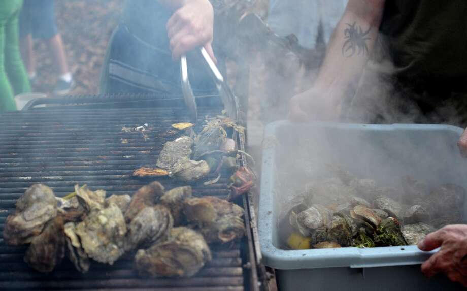 Fresh Gulf oysters, steamed in a Texas Coffee Co. coffee sack, are removed from the grill by Chef Monica Cobb at Slow Food Beaumont's Oysterfest. Beth Rankin/cat5 Photo: Beth Rankin / Beth Rankin