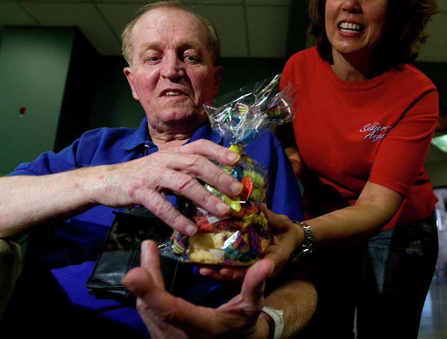 Soldiers' Angels volunteer Judy Johnson presents John Ellise with cookies in honor of his birthday. Baker Ginny Schulin (not pictured) donates cookies to patients of the Michael E. DeBakey VA Medical Center. Photo: Johnny Hanson, Staff / © 2013  Houston Chronicle