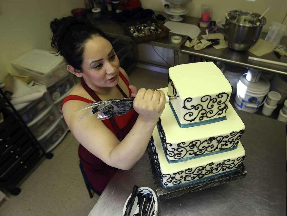 Amanda Morales Decorates A Wedding Cake With Scroll Work At Betty Janeu0027s  Bakeshoppe. Photo: