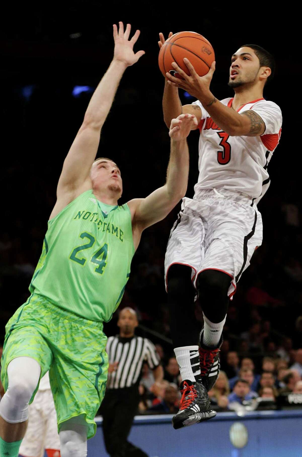 This March 15, 2013, file photo shows Louisville's Peyton Siva (3) driving past Notre Dame's Pat Connaughton (24) during the first half of an NCAA college basketball game at the Big East Conference tournament in New York. The neon-colored jerseys and camouflage-covered shorts debuted by six teams in their post-season conference championships ahead of the NCAA men's basketball tournament weren't well received in the press and social media. The changes happened to be in line with fashion runways and in recreational athleticwear, where highlighter brights and creative camo have been bona fide trends, and alternate uniforms have become part of the college football and basketball landscape, but on the court, these uniforms still made fans cringe.