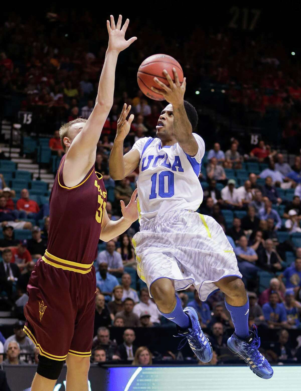 This March 14, 2013, file photo shows UCLA's Larry Drew II (10) as he goes up for a shot against Arizona State's Jonathan Gilling during the first half of a Pac-12 men's tournament NCAA college basketball game in Las Vegas. The neon-colored jerseys and camouflage-covered shorts debuted by six teams in their post-season conference championships ahead of the NCAA men's basketball tournament weren't well received in the press and social media. The changes happened to be in line with fashion runways and in recreational athleticwear, where highlighter brights and creative camo have been bona fide trends, and alternate uniforms have become part of the college football and basketball landscape, but on the court, these uniforms still made fans cringe.