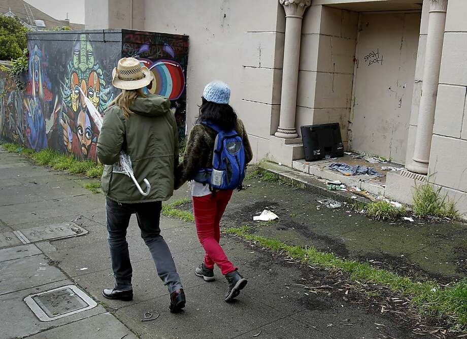 Pedestrians pass litter in a doorway of the old UC Berkeley Extension campus on Haight Street. Photo: Brant Ward, The Chronicle