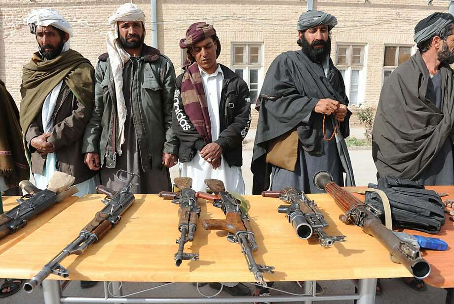 Switching sides:Former Taliban fighters lay down their weapons after joining Afghan government forces during a ceremony in Herat. Photo: Aref Karimi, AFP/Getty Images