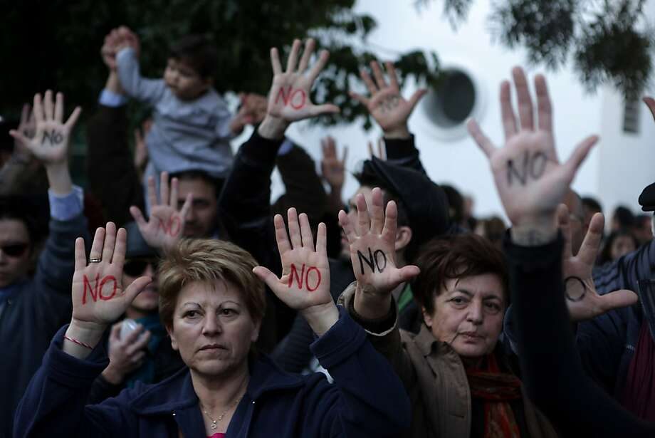 Look, Ma, 'no' hands: How do Cypriots feel about a bailout plan that would allow the government to seize 10 percent of every person's bank account? Against it, hands down. Or rather, up. Photo: Patrick Baz, AFP/Getty Images