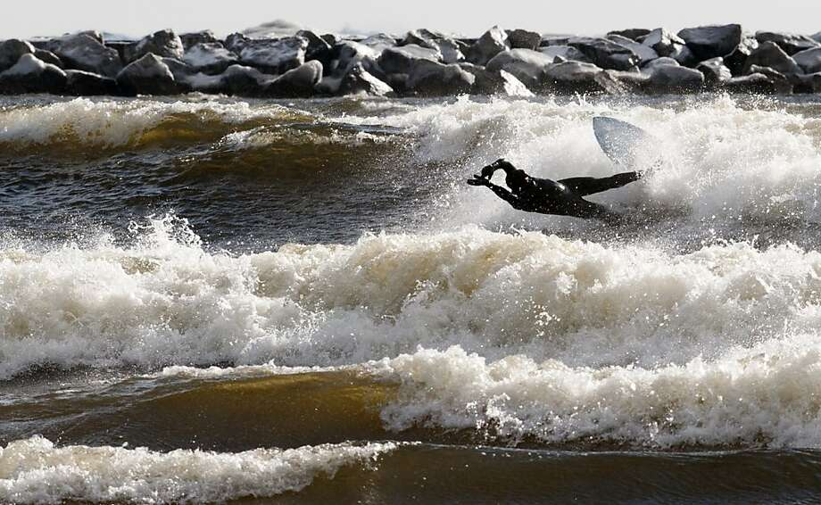 Mistake on the lake:Mike Sabatino wipes out while surfing Lake Michigan at Pere Marquette Park. The last day of winter brought lake-effect snow and high winds that created ideal waves. Photo: Ariana Van Den Akker, Associated Press