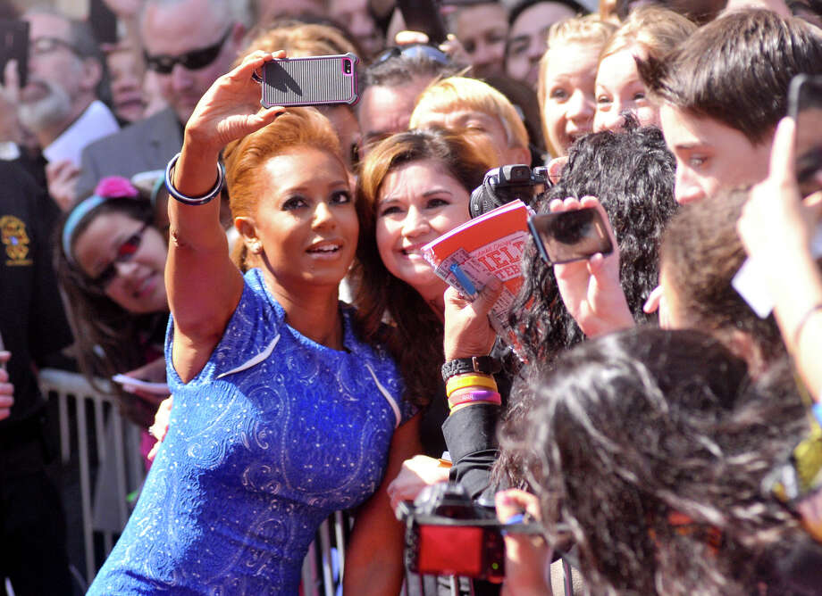 Mel B takes pictures with fans as she arrives on the red carpet in front of the Lila Cockrell Theater for a taping of the television show America's Got Talent Wednesday. Photo: Robin Jerstad