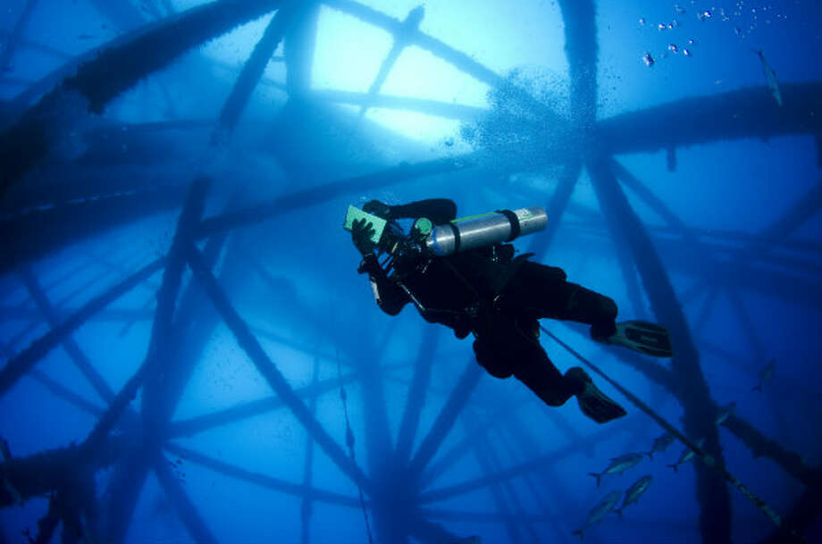 A diver explores a rig that has been turned into an artificial reef in the Gulf of Mexico.