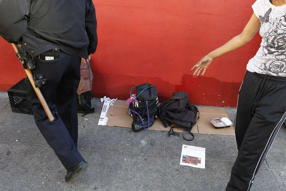 San Francisco police officer Barry Mlaker looks for alcohol in peoples' belongings on Turk Street as he and his parnter officer James Tacchini walk their beat near Market Street in San Francisco, Calif., looking for chronic law breakers on Wednesday, November 14, 2012. Photo: Carlos Avila Gonzalez, The Chronicle