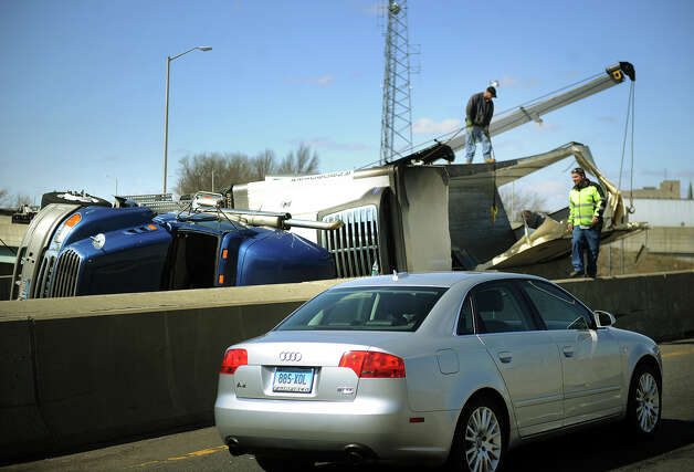 Crews work to remove a tractor-trailer that flipped over on exit 27A northbound off of Interstate 95 in Bridgeport, Conn. on Wednesday March 20, 2013. The accident closed the ramp between the interstate and Route 8 north for several hours. The exit 27A ramp from I-95 north to Route 8 north re-opened at about 3:40 p.m., easing congestion caused by the crash and a resulting detour that was in effect for most of the day. Photo: Brian A. Pounds / Connecticut Post