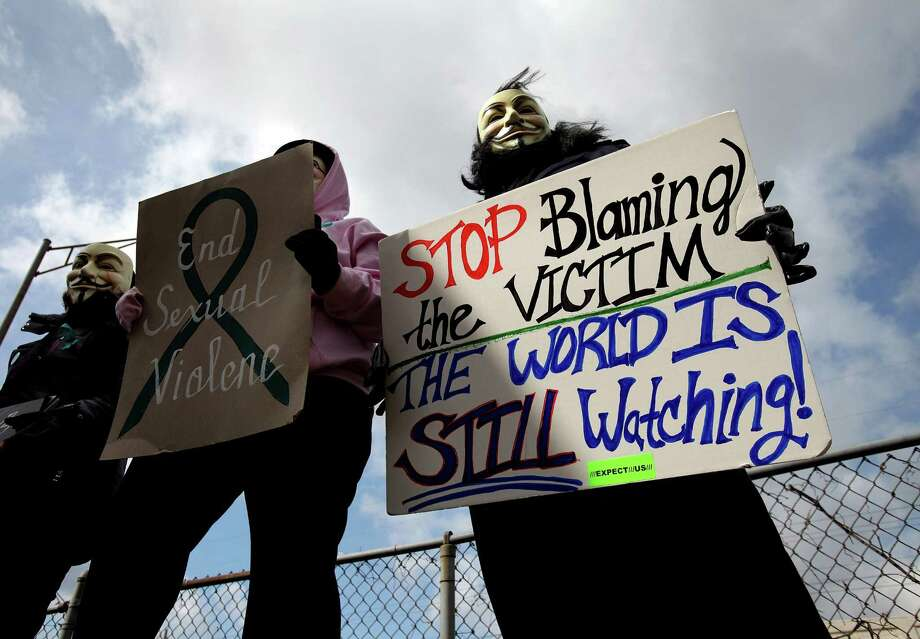 Protesters, hiding their identities, hold signs outside the Jefferson County Justice Center and Jail in Steubenville, Ohio. The city's controversial rape case went viral in social media. Photo: Lisa DeJong, Associated Press