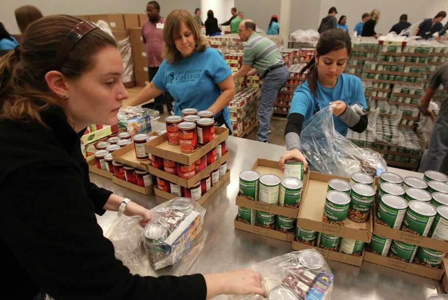 "Volunteers Megan Schwartz, Claudia Maldonado and Maria Aguire quickly bag the ""Backpack Buddy"" for needy children at the Houston Food Bank on Thursday, Dec. 20, 2012, in Houston. Houston Food Bank is struggling to keep it's pantries full because of a decline in government donations over the last two years. ( Mayra Beltran / Houston Chronicle ) Photo: Mayra Beltran, Staff / © 2012 Houston Chronicle"