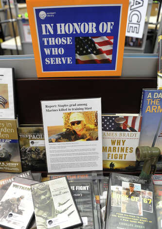 The Westport Public Library has set up a table on Wednesday March 20 2013 to pay respect to the military in general and US Marine Roger Muchnick specifically, who was killed in a live fire training exercise in Nevada. Photo: Christian Abraham / Connecticut Post
