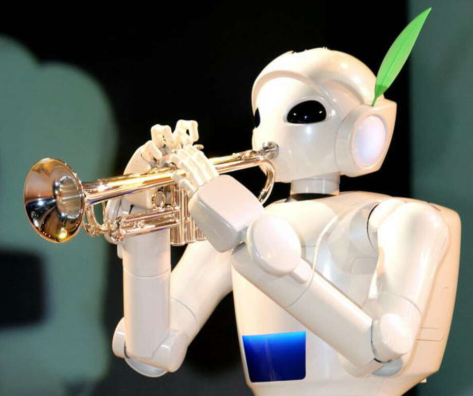 "Japanese auto giant Toyota Motor's music playing robot blows a trumpet at a preview for the upcoming ""EXPO 2005 AICHI"" at the company's showroom in Tokyo, 03 December 2004. The robot trumpeter, 1.45m in height and weighing 40kg, can walk and play music with its artificial lips.   AFP PHOTO/Yoshikazu TSUNO Photo: YOSHIKAZU TSUNO, Getty / 2004 AFP"
