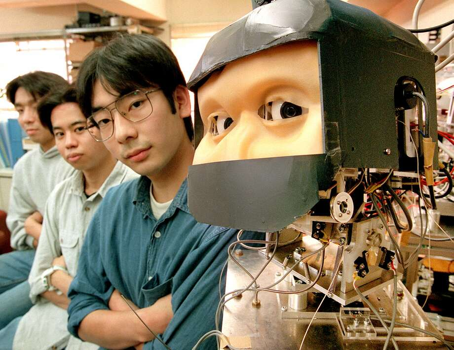 The Eye Robot (R) and students of Japan's Waseda University have the same look with their eyes at their laboratory in Tokyo 02 November.  Yoshiyuki Miwa, Professor of the Waseda University, developed the Eye Robot which expresses human feelings of joy, sadness, anger and embarrasment.    AFP  PHOTO Photo: YOSHIKAZU TSUNO, Getty / AFP