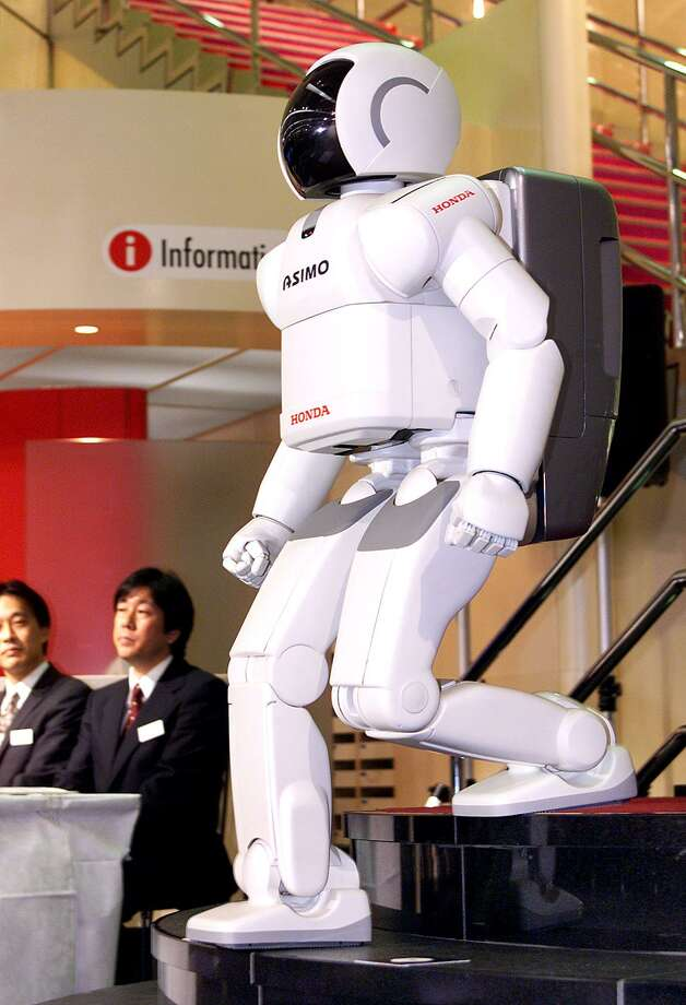 Japan's auto giant Honda's humanoid robot, Asimo, walks down the steps as Honda unveils the new and improved version of the robot featuring advanced frexible walking technology with a simplified system to use in public areas during a press preview at the company's headquarters in Tokyo, 12 November 2001.  Honda will start a rental service of the Asimo from next April with a rental fee of 20 million yen (167 million USD) for a year.  AFP PHOTO/Yoshikazu TSUNO Photo: YOSHIKAZU TSUNO, Getty / AFP