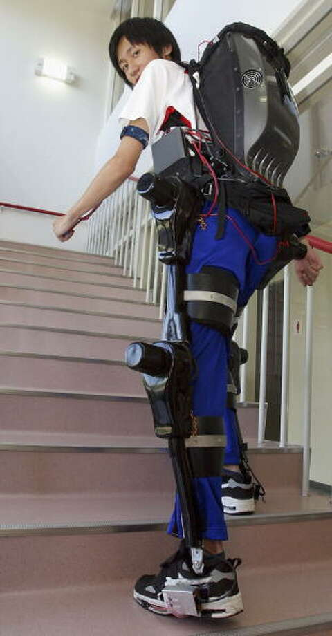 A man walks up stairs demonstrating a prototype of a powered suit, HAL (Hybrid Assistive Leg) at the University of Tsukuba, on September 21, 2004 in Tsukuba, Ibaraki Prefecture, Japan. HAL is a body-fit robot that helps people with walking and sitting up and down. The main feature of this suit is that it has sensors attached to the skin of the user's legs that read the electrical signals sent from the brain to the muscles when the user plans to make a movement, so that the HAL is able to assist with an action slightly before the action is actually taken. It's planned market release is in a year's time, at a cost of 1,500,000 Yen (roughly US$13,600) for individuals and 15,000,000 Yen for medical institutes. Photo: Junko Kimura, Getty / 2004 Getty Images