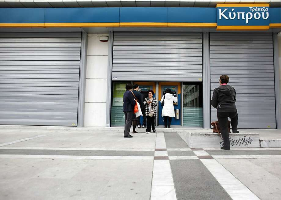 People wait to use ATMs outside a closed bank branch at the Bank of Cyprus in Athens. Photo: Kostas Tsironis, Bloomberg