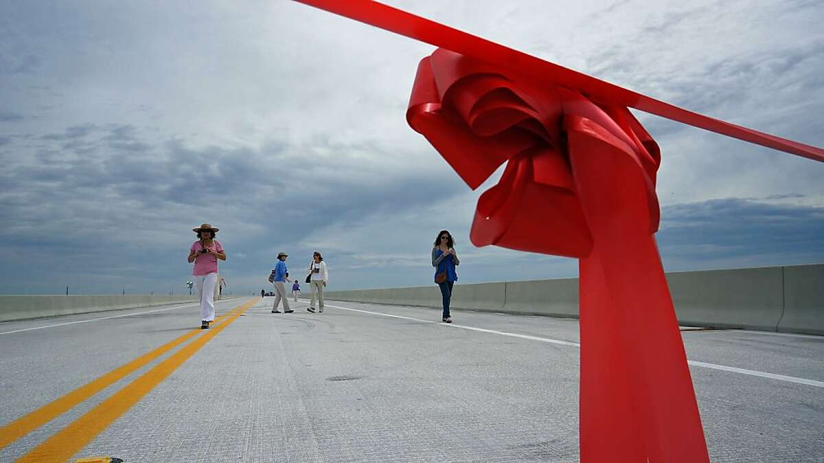 The red ribbon waiting to be cut frames people walking along the new Tamiami Trail Bridge in the Everglades, Tuesday, March 19, 2013. The Tamiami Trail bridge in the Everglades, which will allow water from the River of Grass to flow from north of the Tamiami Trail to the south, was dedicated Tuesday in a ceremony attended by Secretary of the Interior Ken Salazar. The one-mile-long bridge is a few miles west of Krome Ave and is the first of several planned bridges intended to increase water flowing into Everglades National Park. (AP Photo/The Miami Herald, Chuck Fadely) MAGS OUT