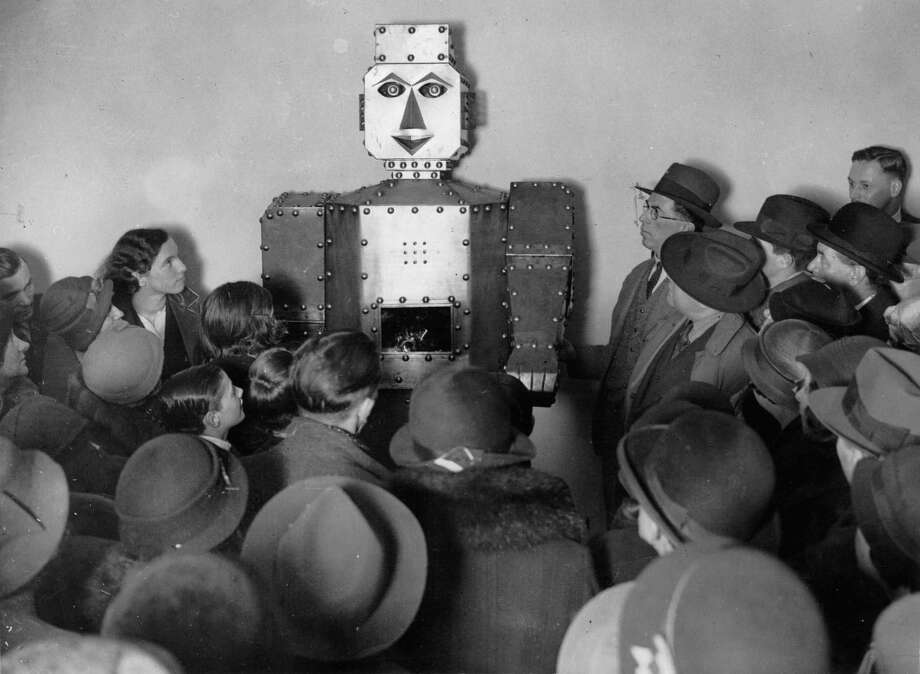 Visitors to Selfridge's store in London admiring the electric robot which answers questions and tells fortune. It has been installed in connection with the store's twenty-fifth anniversary. England. Photograph. 1934. Photo:  Anonym, Getty / IMAGNO/Austrian Archives (S)