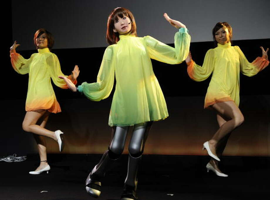 "A 1.58m tall humanoid robot ""HRP-4C"" of Japan's Advanced Industrial Science and Technology (AIST) sings and dances with performers at the Digital Contents Expo in Tokyo on October 17, 2010.  AIST developed the entertainment software called Choreonoid, formed from choreograph and humanoid.   AFP PHOTO / Yoshikazu TSUNO Photo: YOSHIKAZU TSUNO, Getty / 2010 AFP"