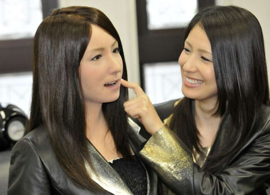 "A model (R) pokes the face of a humanoid robot called ""Geminoid-F"" (L) shaped to resemble the model at a press conference in Osaka, on April 3, 2010. Geminoid-F, designed and built by Osaka University professor Hiroshi Ishiguro and Japan's robot maker Kokoro, is equipped with 12 actuators, powered by air pressure, and her motion can be synched to imitate that of a real human being. AFP PHOTO / Yoshikazu TSUNO Photo: YOSHIKAZU TSUNO, Getty / 2010 AFP"