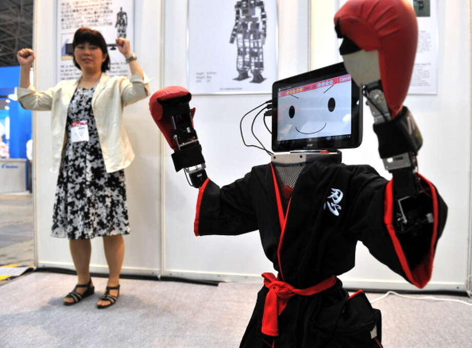 """Japanese robot venture RT corporation's humanoid robot """"RIC90"""", dressed in a ninja costume, mimics actions of a company employee (L) during a demonstration at the Robotech exhibition in Tokyo on July 11, 2012.  The robot's head is made of a tablet PC.   AFP PHOTO / Yoshikazu TSUNO Photo: YOSHIKAZU TSUNO, Getty / 2012 AFP"""