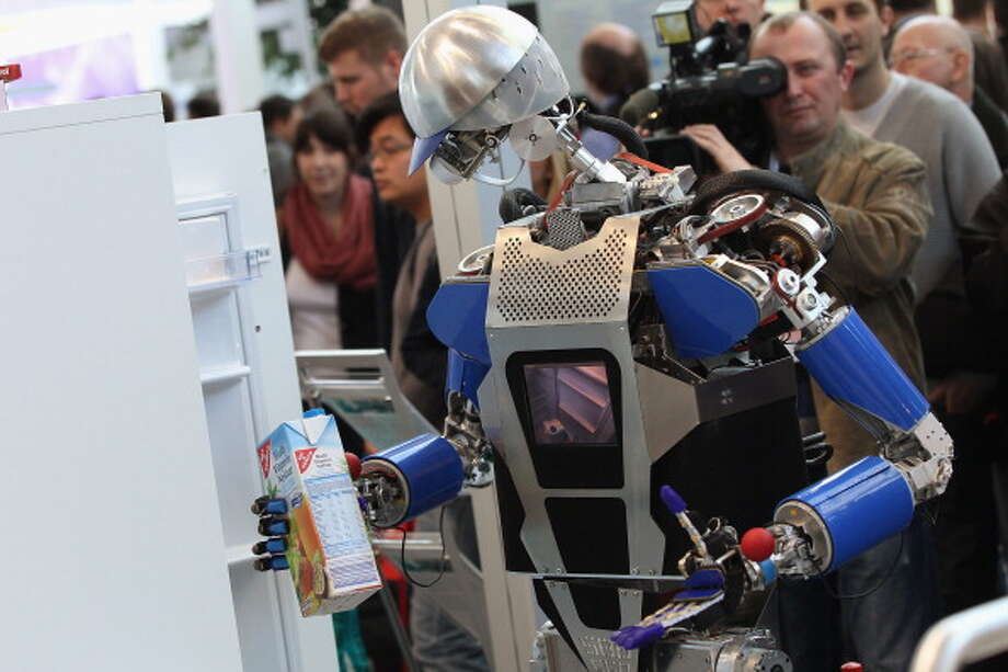 A robot developed by the Karlsruhe Institute of Technology retrieves a carton of juice in a presentation on the first day of the CeBIT 2012 technology trade fair on March 6, 2012 in Hanover, Germany. CeBIT 2012, the world's largest information technology trade fair, will run from March 6-10, and advances in cloud computing and security are major features this year. Photo: Sean Gallup, Getty / 2012 Getty Images