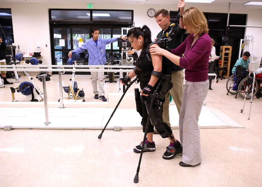 Paralysis victim Stephanie Sablan (L) is helped by physical therapists Shonna Moran (R) and Darrell Musick (C) as she walks using eLEGS robotic legs at Santa Clara Valley Medical Center on May 25, 2011 in San Jose, California.  Sablan, 24, was paralyzed from the waist down earlier this year when she was in a car accident and has begun using the newly developed eLEGS made by Berkeley Bionics. The robot-like battery powered eLEGS fit over clothing and enables people with paralysis to stand up and walk again. Photo: Justin Sullivan, Getty / 2011 Getty Images