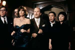 "The cast of ""Clue,"" based on the board game: Michael McKean as Mr. Green, Christopher Lloyd as Professor Plum, Lesley Ann Warren as Miss Scarlet, Martin Mull as Col. Mustard,  Tim Curry as Wadsworth, Madeline Kahn as Mrs. White"