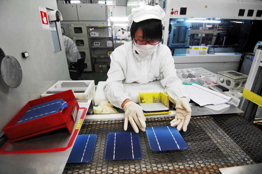 A worker inspects solar panels at a Suntech plant. Photo: Shen Peng, SUB / Xinhua