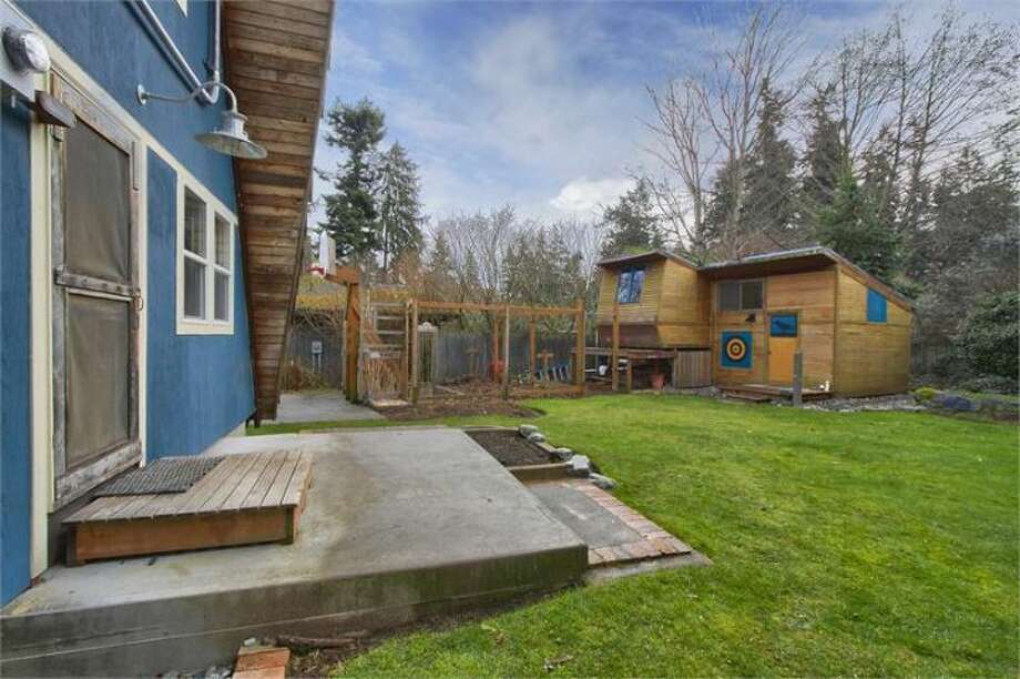 Back yard of 11661 N.E. Yeomalt Point Drive, on Bainbridge Island. The 962-square-foot A-frame house, built in 1963, has two bedrooms, one bathroom, lofted, exposed-wood ceilings, a wall of windows, a front deck, a back patio and a backyard craft shop on a 9,148-square-foot lot with access to a community beach. It's listed for $284,000, although a sale is pending. Photo: Courtesy Wendy Indvik And Jim Lundwall/Windermere Real Estate