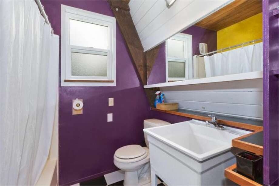 Bathroom of 11661 N.E. Yeomalt Point Drive, on Bainbridge Island. The 962-square-foot A-frame house, built in 1963, has two bedrooms, one bathroom, lofted, exposed-wood ceilings, a wall of windows, a front deck, a back patio and a backyard craft shop on a 9,148-square-foot lot with access to a community beach. It's listed for $284,000, although a sale is pending. Photo: Courtesy Wendy Indvik And Jim Lundwall/Windermere Real Estate