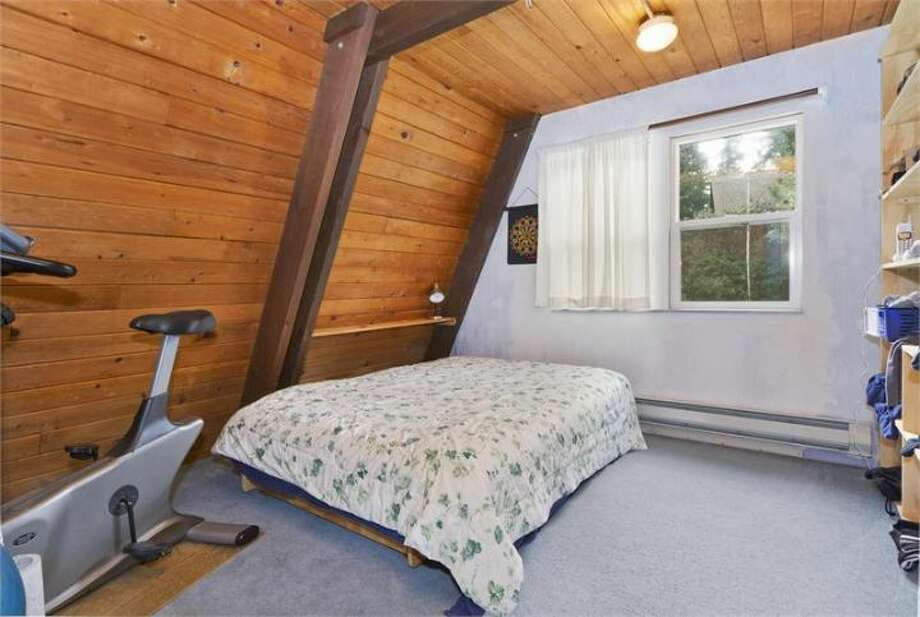 Bedroom of 11661 N.E. Yeomalt Point Drive, on Bainbridge Island. The 962-square-foot A-frame house, built in 1963, has two bedrooms, one bathroom, lofted, exposed-wood ceilings, a wall of windows, a front deck, a back patio and a backyard craft shop on a 9,148-square-foot lot with access to a community beach. It's listed for $284,000, although a sale is pending. Photo: Courtesy Wendy Indvik And Jim Lundwall/Windermere Real Estate