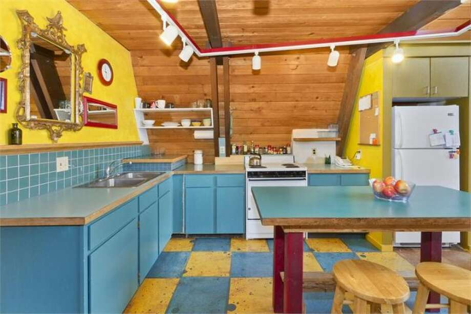 Kitchen of 11661 N.E. Yeomalt Point Drive, on Bainbridge Island. The 962-square-foot A-frame house, built in 1963, has two bedrooms, one bathroom, lofted, exposed-wood ceilings, a wall of windows, a front deck, a back patio and a backyard craft shop on a 9,148-square-foot lot with access to a community beach. It's listed for $284,000, although a sale is pending. Photo: Courtesy Wendy Indvik And Jim Lundwall/Windermere Real Estate