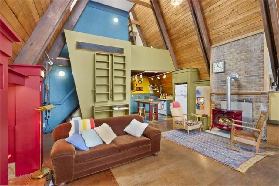 Living room of 11661 N.E. Yeomalt Point Drive, on Bainbridge Island. The 962-square-foot A-frame house, built in 1963, has two bedrooms, one bathroom, lofted, exposed-wood ceilings, a wall of windows, a front deck, a back patio and a backyard craft shop on a 9,148-square-foot lot with access to a community beach. It's listed for $284,000, although a sale is pending. Photo: Courtesy Wendy Indvik And Jim Lundwall/Windermere Real Estate