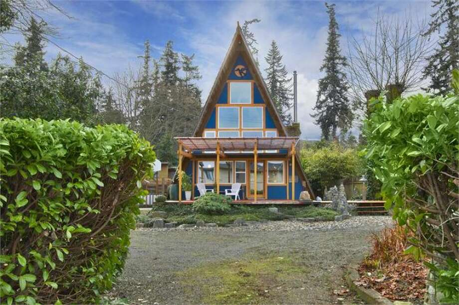 Front of 11661 N.E. Yeomalt Point Drive, on Bainbridge Island. The 962-square-foot A-frame house, built in 1963, has two bedrooms, one bathroom, lofted, exposed-wood ceilings, a wall of windows, a front deck, a back patio and a backyard craft shop on a 9,148-square-foot lot with access to a community beach. It's listed for $284,000, although a sale is pending. Photo: Courtesy Wendy Indvik And Jim Lundwall/Windermere Real Estate