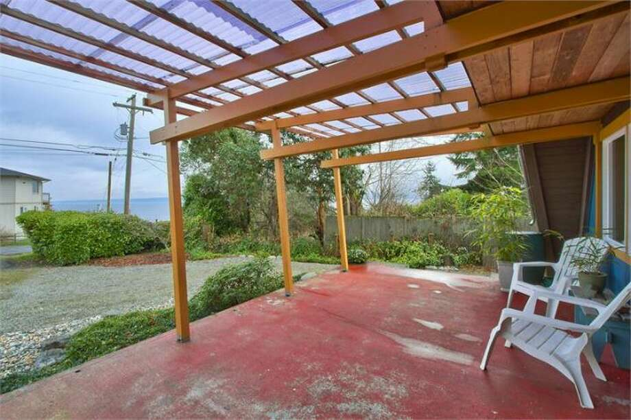 Front deck of 11661 N.E. Yeomalt Point Drive, on Bainbridge Island. The 962-square-foot A-frame house, built in 1963, has two bedrooms, one bathroom, lofted, exposed-wood ceilings, a wall of windows, a back patio and a backyard craft shop on a 9,148-square-foot lot with access to a community beach. It's listed for $284,000, although a sale is pending. Photo: Courtesy Wendy Indvik And Jim Lundwall/Windermere Real Estate