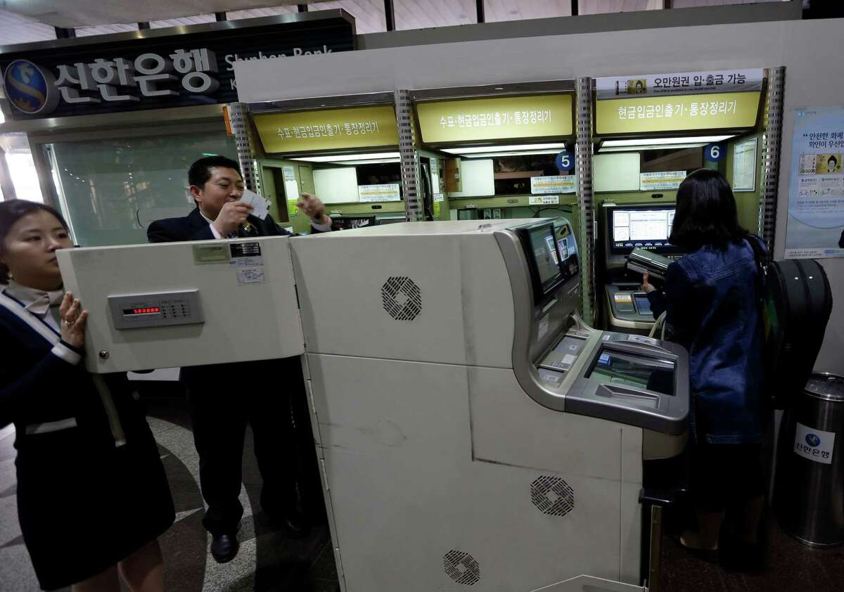 Bank clerks check an automated teller machine after computer networks were fixed Wednesday after a suspected cyberattack in Seoul, South Korea.