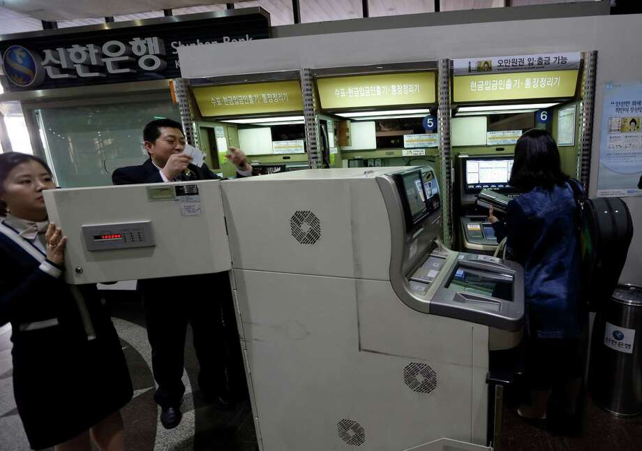 Bank clerks check an automated teller machine after computer networks were fixed Wednesday after a suspected cyberattack in Seoul, South Korea. Photo: Lee Jin-man, STF / AP