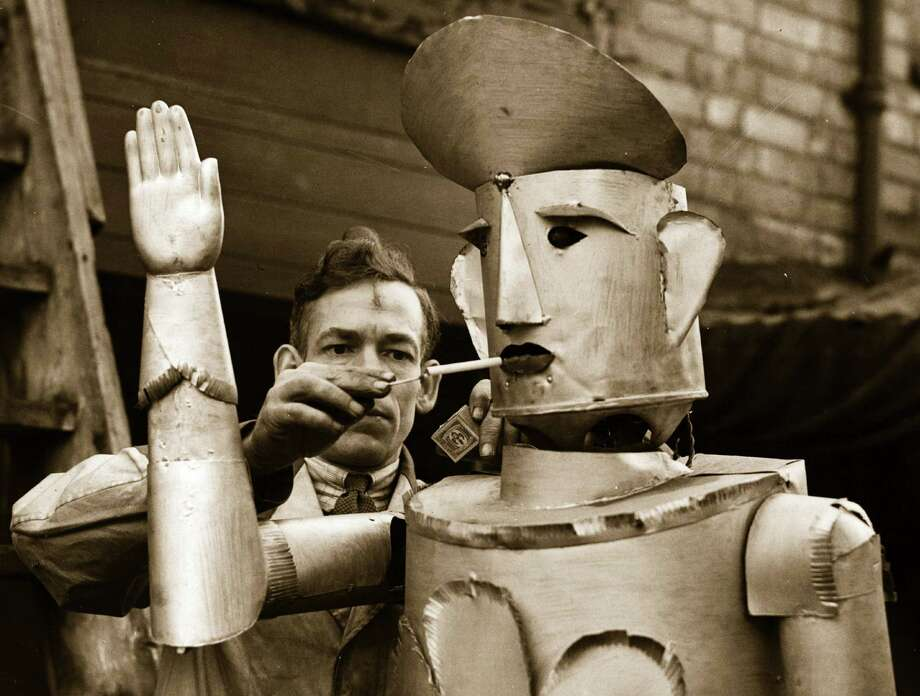 15th January 1939:  Mr Charles Lawson, an electrical engineer of Kettering lights his robot's cigarette. Photo: Fox Photos, Getty / Hulton Archive