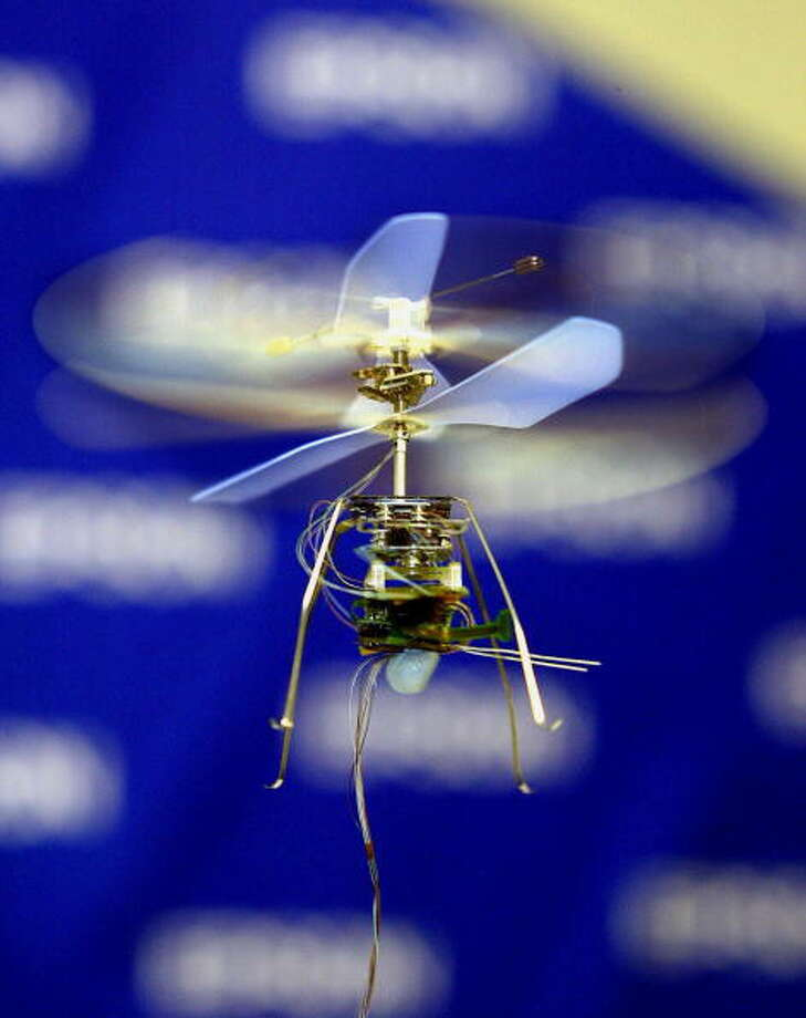 "Japan's electronics giant Seiko Epson unveils the world's smallest and lightest radio controled helicopter ""Micro Flying Robot"", 7cm in height, 13cm in diameter of rotors and weighing only 8.9g, equipped with four micro actuators to drive two rotors and stabilizing units at the International Robot Exhibition in Tokyo, 19 November 2003.    AFP PHOTO / Yoshikazu TSUNO Photo: YOSHIKAZU TSUNO, Getty / 2003 AFP"