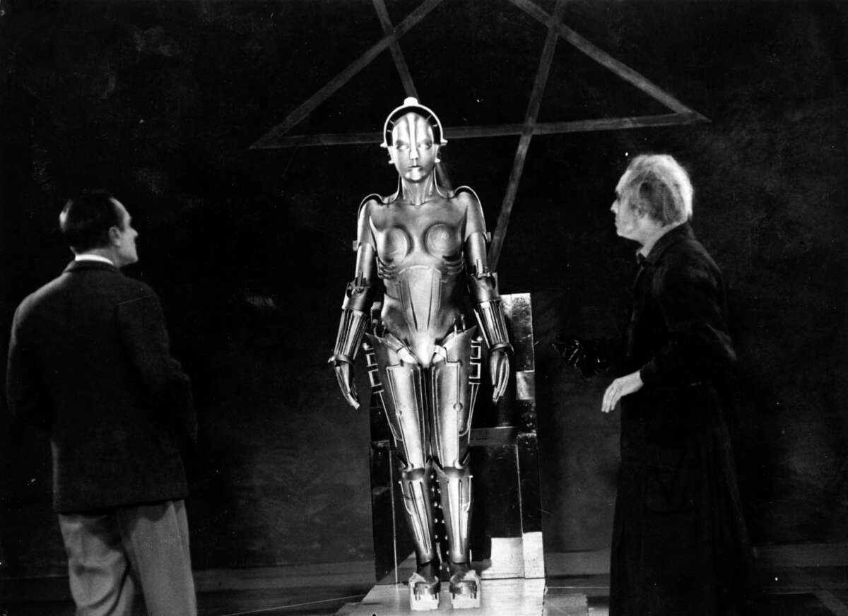 Alfred Abel and Rudolf Klein-Rogge inspect the female robot in a scene from the film 'Metropolis', a vision of life in the year 2000 where workers in a modernistic city labour underground. The film was directed by Fritz Lang for UFA.